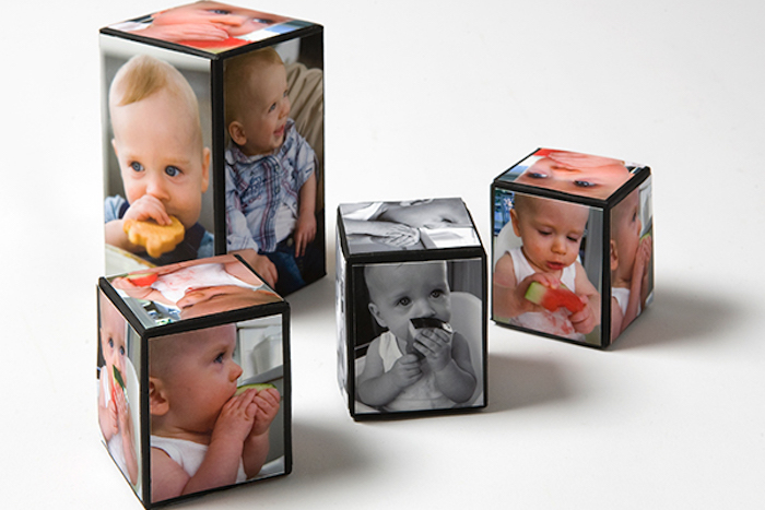black and white and colored photos of a baby, covering four cube-shaped decorations, in different sizes, mother's day gifts for grandma