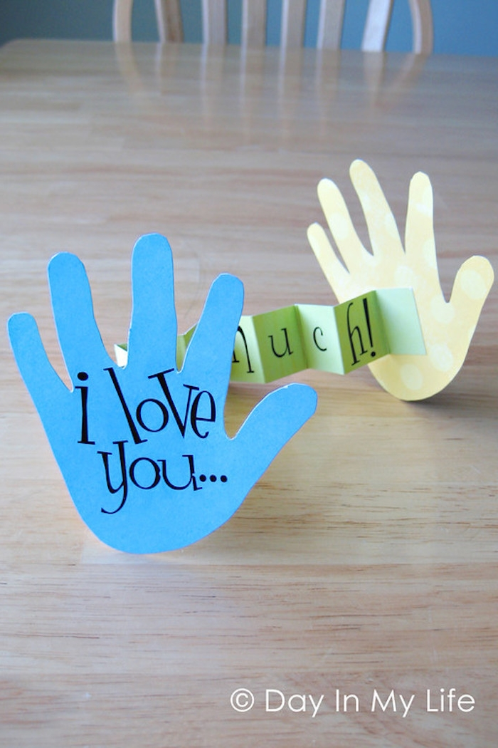 i love you this much, written with black, on two paper cutouts, shaped like child's hands, connected with green piece of folding paper