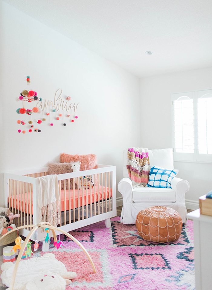 coral pink and beige bedding, and two matching fluffy cushions, in white crib, on pink carpet, with black and orange motifs, baby girl themes, peruvian aesthetic