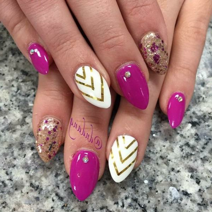 combination of pink-purple, gold and white, on short stiletto nails, with golden stripes and glitter, and small rhinestones