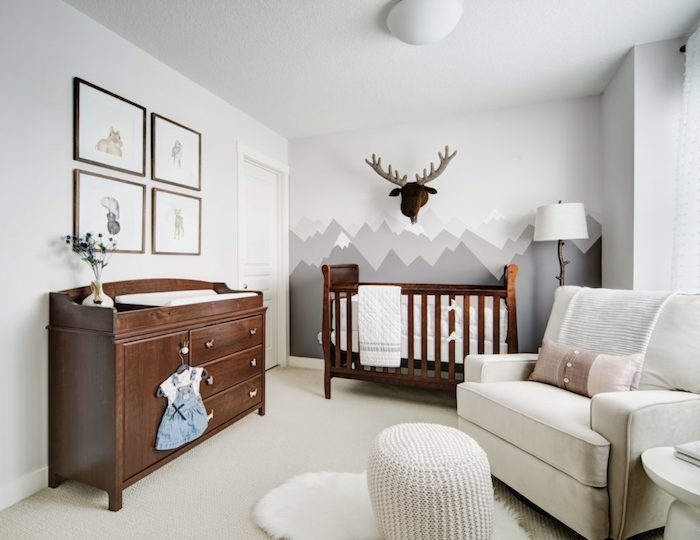 neutral colors in nursery room, dark wooden crib and matching changing table, four framed images, wall mural with gray mountains, pale white armchair