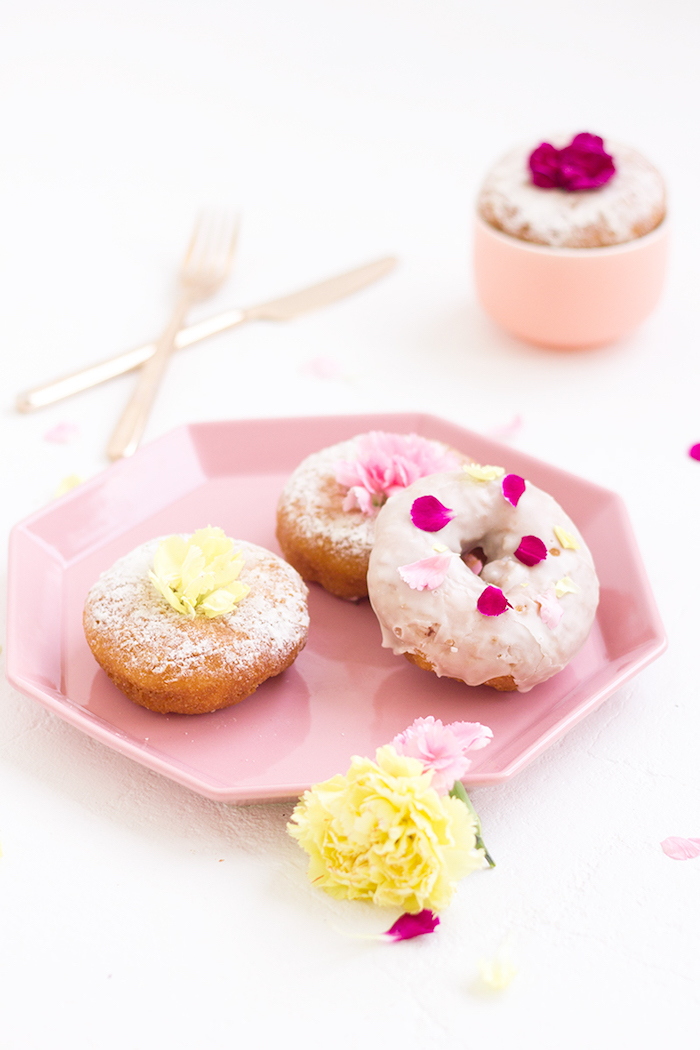 pastries or donuts, some dusted with powdered sugar, and one covered with pink glazing, top 10 mother's day gift ideas, decorated with flower petals