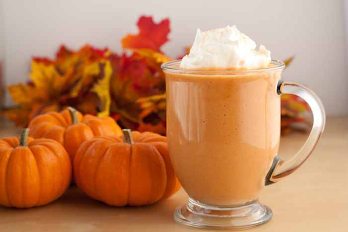 mini pumpkins and dried autumn leaves, near a clear glass with handle, filled with pale orange drink, topped with whipped cream, easy smoothie recipes