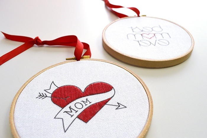 close up of two round, white peaces of cloth, embroidered with red and black thread, with hearts and messages for mom, top 10 mother's day gift ideas, with red ribbons