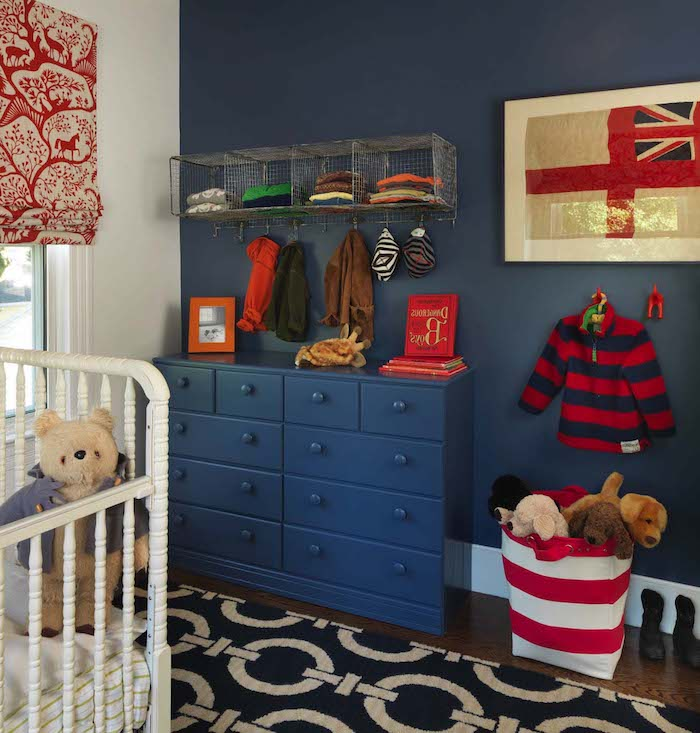 striped red and blue child's jumper, hanging on dark blue wall, with matching chest of drawers, white crib and teddy bear, boys room ideas