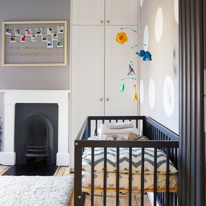 minimalist boys room ideas, gray and white walls, black and white fireplace, black wooden crib, mobile with animals