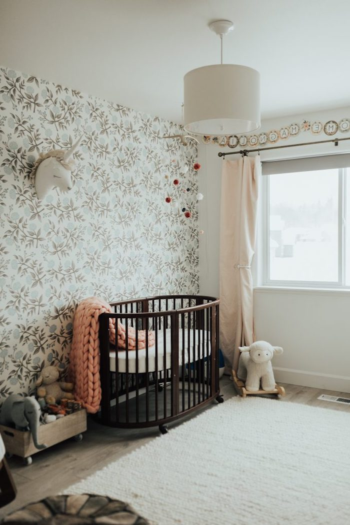 antique dark wooden baby crib, and pink chunky-knit cozy, in room with gentle floral wallpaper, baby girl nursery ideas, pale pink curtains, and various toys