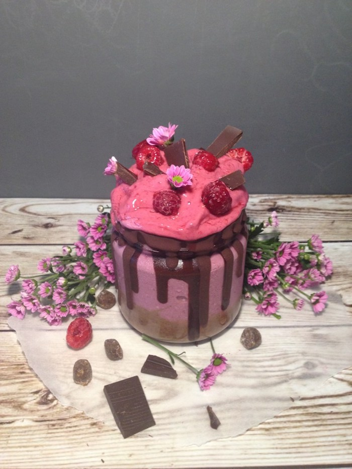 milk chocolate pieces, raspberries and small flowers, topping a pink creamy dessert, how to make a fruit smoothie, more flowers and berries nearby