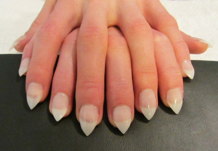 two hands placed on top of each other, with sharp stiletto nails, nude pink bottom part, and white tips, french manicure style