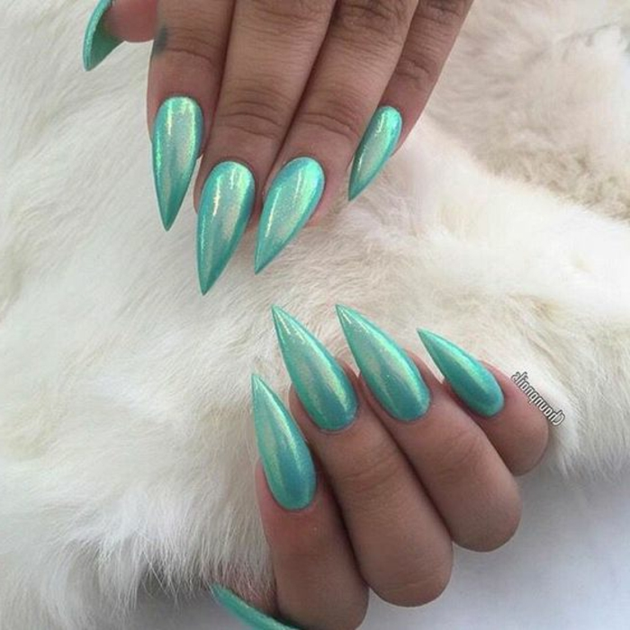 mermaid stiletto nails, long and sharp, painted in iridescent, teal blue nail polish, on two hands, holding soft white fur