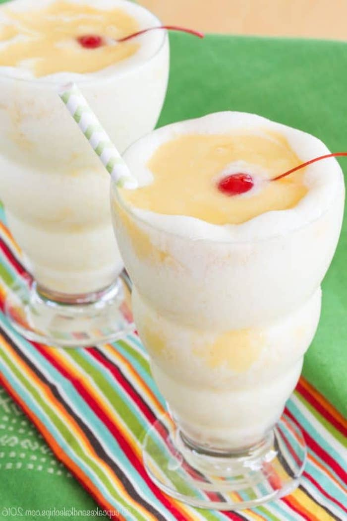 fluffy and frothy drink, in white and yellow, topped with a straw and a maraschino cherry, fruit smoothie recipes, blended pina colada