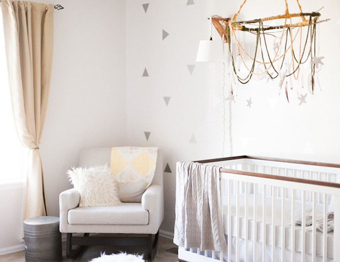 rocking armchair in white, near wooden crib in white and brown, in bright nursery, decorated with light neutral colors