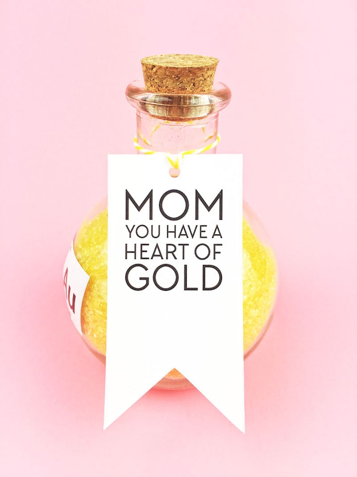 round bottle made of glass, with cork stopper, containing yellow bath salts, mothers day gifts, white label with message to mom