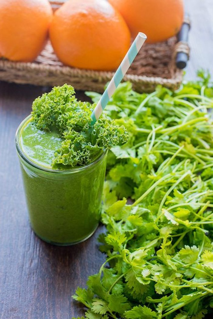 kale and spinach smoothie, with blended parsley, in a clear glass, decorated with kale leaf and straw, oranges in background