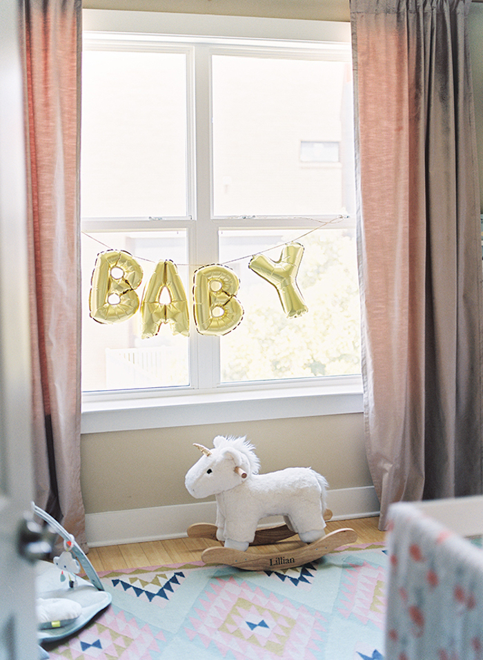 baloons in shiny golden color, shaped like letters, spelling the word baby, hung on a window, with pastel pink curtains, baby girl themes, rocking unicorn toy