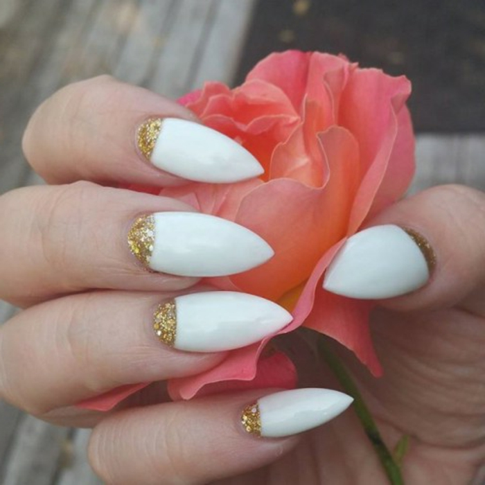 hand with long sharp nails, stilleto nail designs, painted in white nail polish, and decorated with golden glitter, holding a faux pink flower