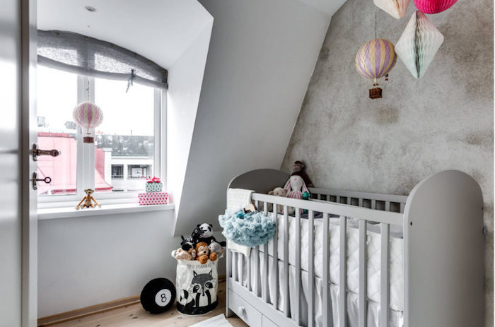 modern girl nursery themes, pale gray baby crib, in room with white and gray wash walls, lots of toys in pastel colors