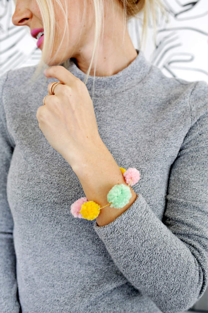 blonde woman with tied back hair, wearing gray jumper, and cyclamen pink lipstick, with bracelet made of pompoms, gift ideas for mom