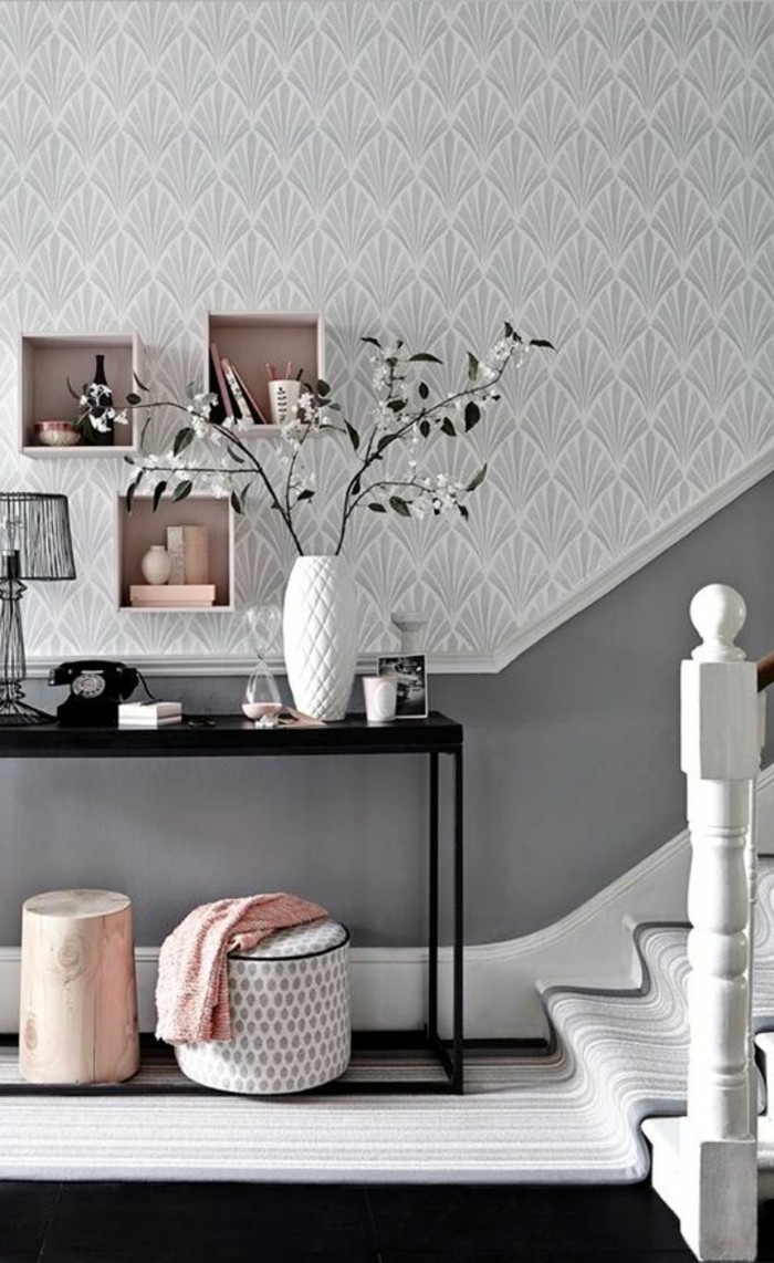 landing or hallway, with pale gray ornate wallpaper, and dark gray paneling, near stairway with light striped rug, pale pink and white decorations