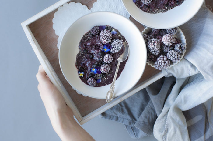 tray with two bowls, containing blended fruits, decorated with frozen blackberries, and tiny blue flowers, healthy breakfast smoothies, small dish with more frozen blackberries