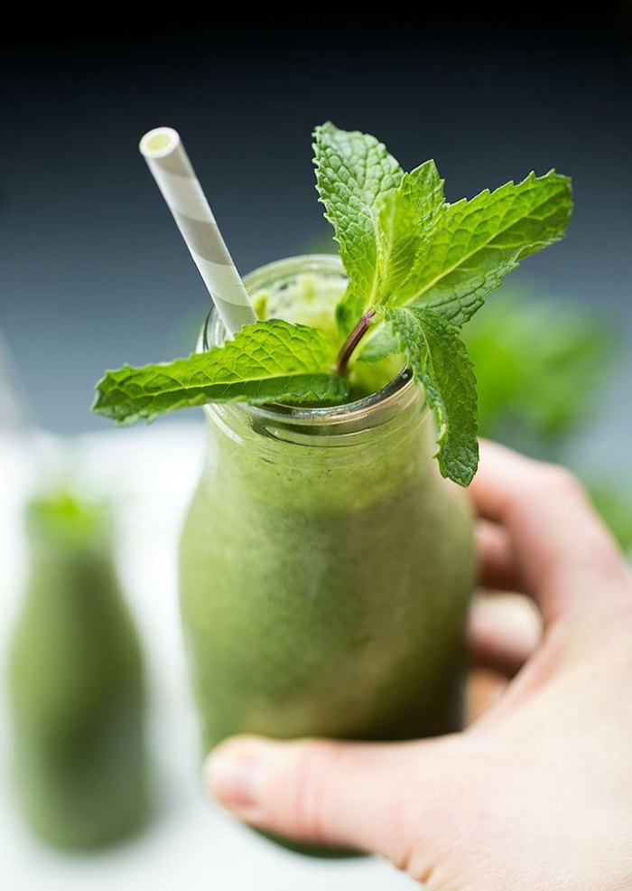 fresh spearmint stalk, inside a small bottle, green smoothie recipe, filled with a green blended drink, and held by a human hand