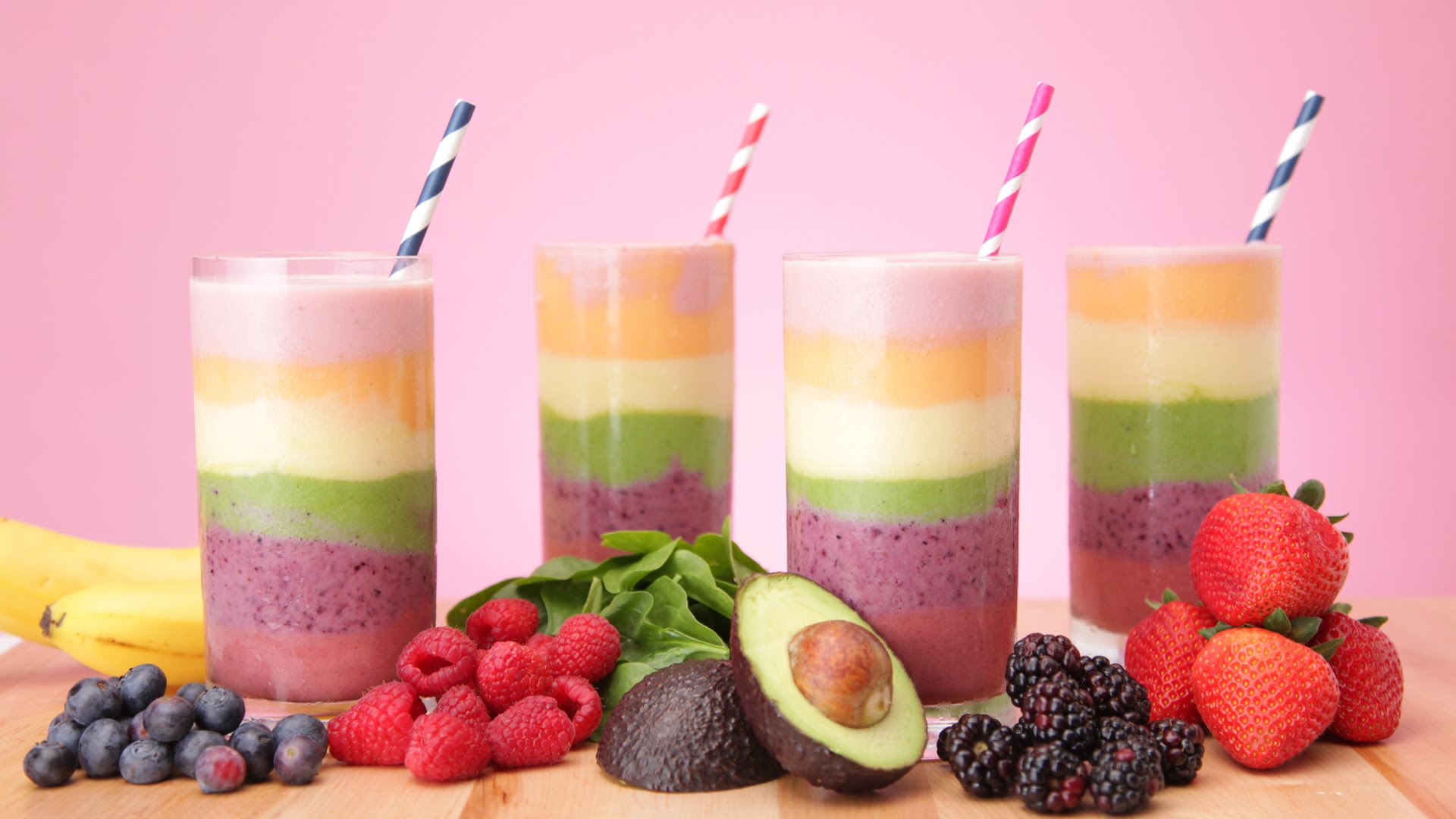 avocado and grape, blackberry and raspberry, banana and spinach smoothie, layered fruit and spinach smoothie, in four glasses with straws