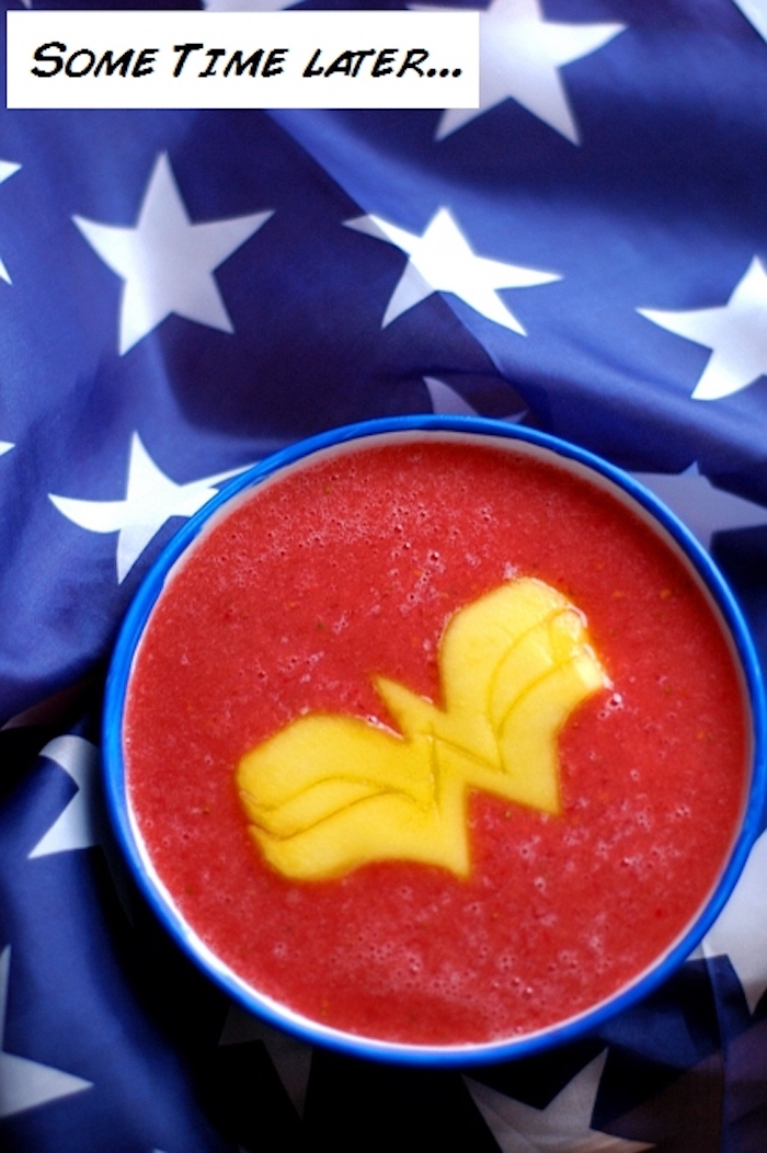 wonder woman-inspired fruit drink, how to make a fruit smoothie, blended berries topped with a w-shaped mango slice, blue cloth with white stars in background
