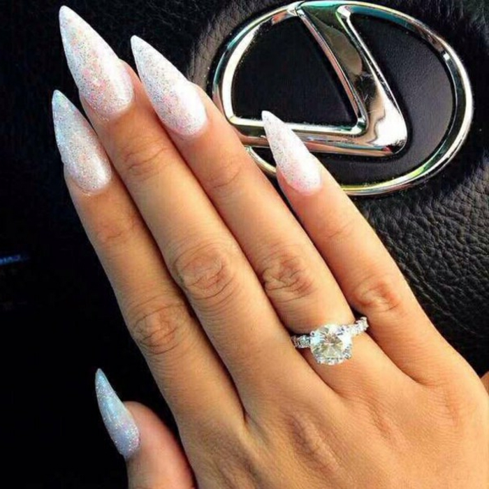 diamond ring on hand with long, slender fingers and sharp, stiletto acrylic nails, covered in iridescent silver glitter, lexus logo in background