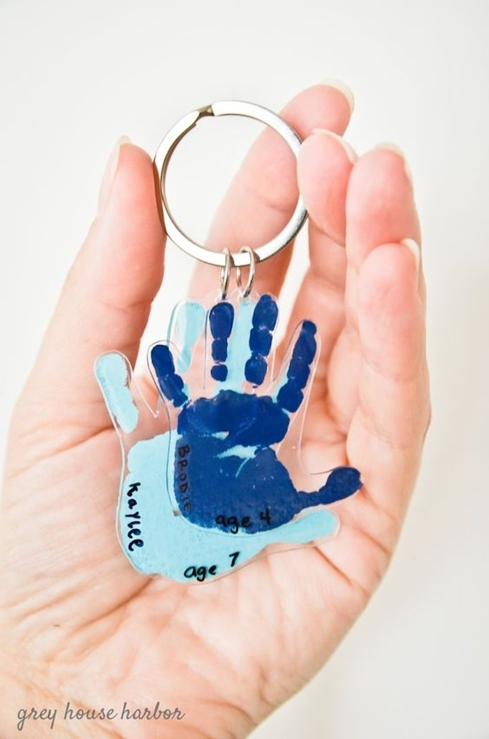 navy and light blue baby hand prints, coated in clear plastic, and attached to a metal keyring, mother's day gifts for grandma, held by a person's hand