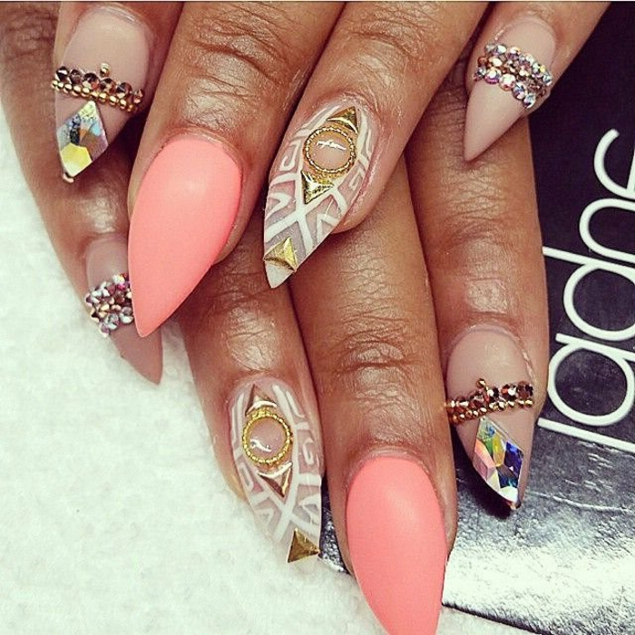 colorful sharp nails, with clear and neon pink nail polish, lavishly decorated with rhinestone and pearl stickers, golden details and hand-drawn white motifs