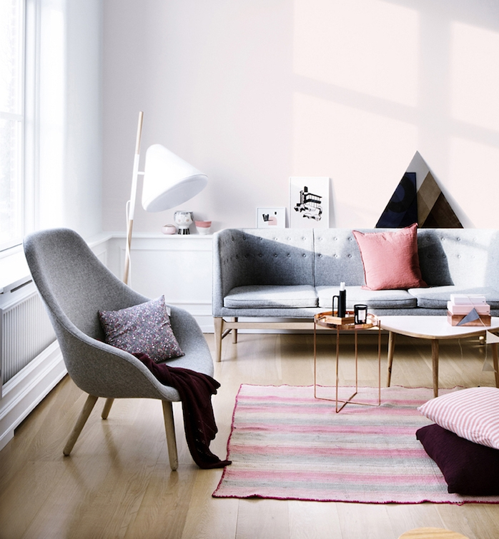 pinkish gray walls, with white paneling, light wooden laminate floor, pale gray sofa and armchair, colors that go with gray walls, striped rug