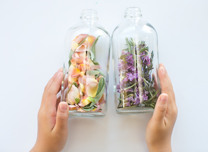 child's hands holding two clear bottles, made of plastic or glass, filled with rose petals and sage, lilac and rosemary, mother's day gift ideas, home-made perfume