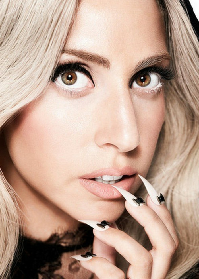 close-up of lady gaga, platinum blonde hair, and nude pink lipstick, black eyeliner and long, sharp pointy nails, painted in white, and decorated with little, black bow-shaped ornaments