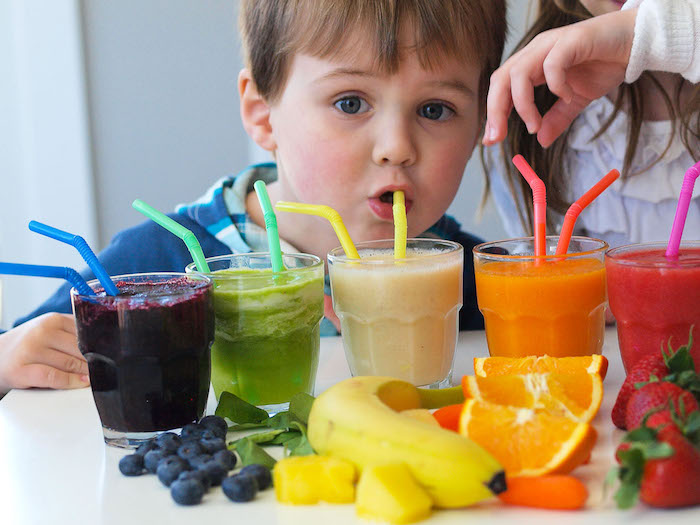 toddler drinking juice from a straw, near five clear glasses, each containing a juice in a different color, banana and orange, berries and carrots, spinach smoothie