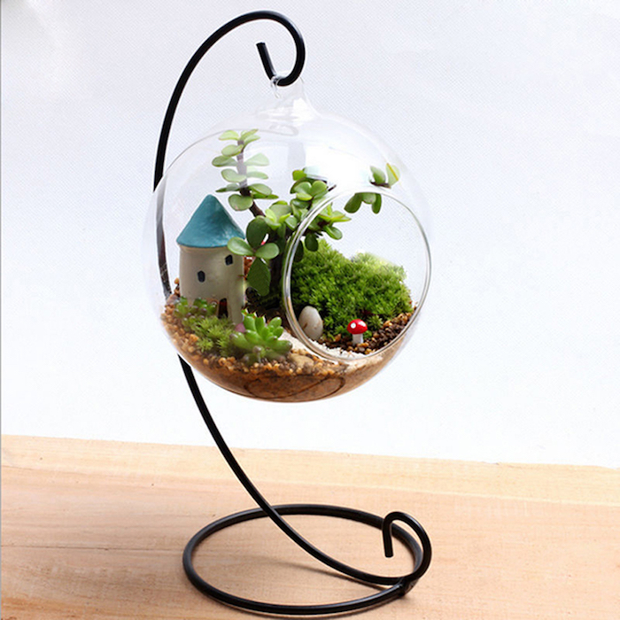 mushroom and house, tiny painted figurines, inside a hanging terrarium, made of glass, on a black metal stand, filled with succulents and moss