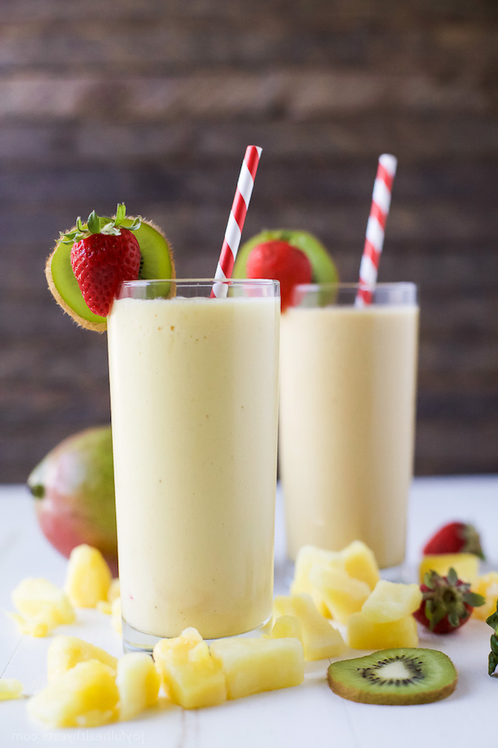 mango chunks and kiwi slices, strawberries and a whole mango, near two glasses, decorated with kiwi and strawberries, filled with creamy yellow liquid, smoothie recipes