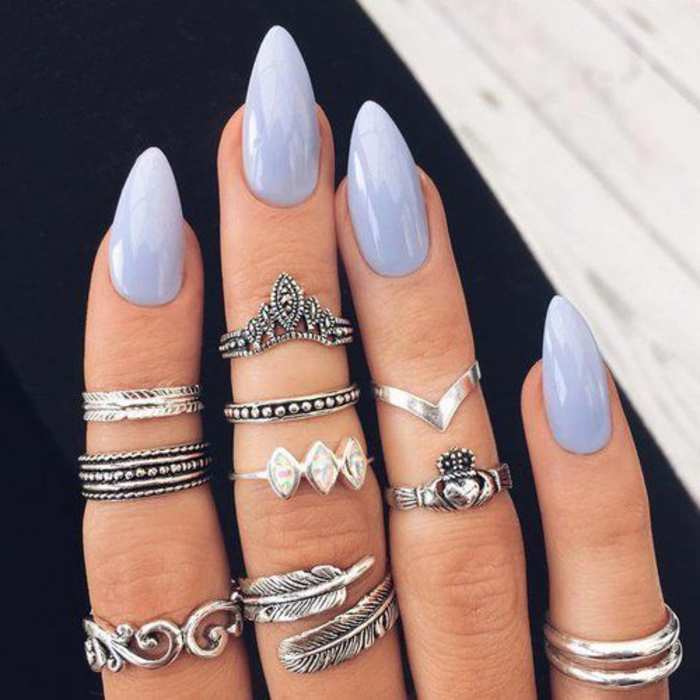 many boho-style decorative silver rings, on four fingers, painted in pale, milky violet nail polish
