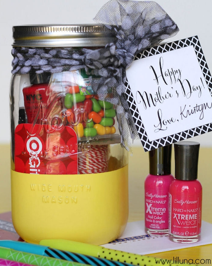 pens in different colors, and two bottles of nail polish, in cyclamen and red, near mason jar, half colored in yellow, containing mother's day goodies