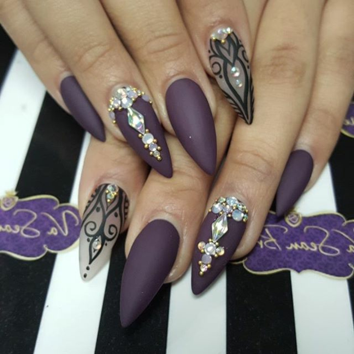long stiletto nails, painted in matte purple, and clear nail polish, with black hand-drawn details, and iridescent nail decal gems