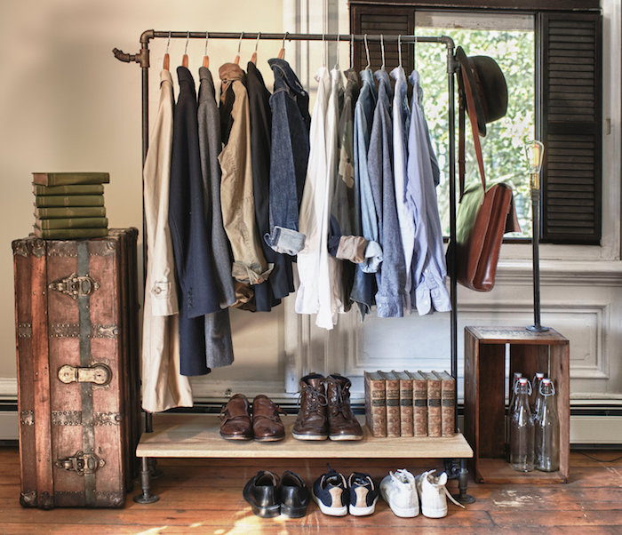 simple clothes rack, made of metal and a wooden shelf, with various clothes items for men, shirts and blazers, leather shoes and sneakers, alternative to closet
