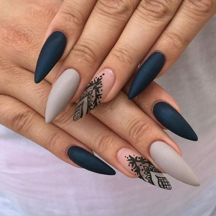 grey clear and black matte nail polish, on long stiletto nails, with black hand-painted decorations