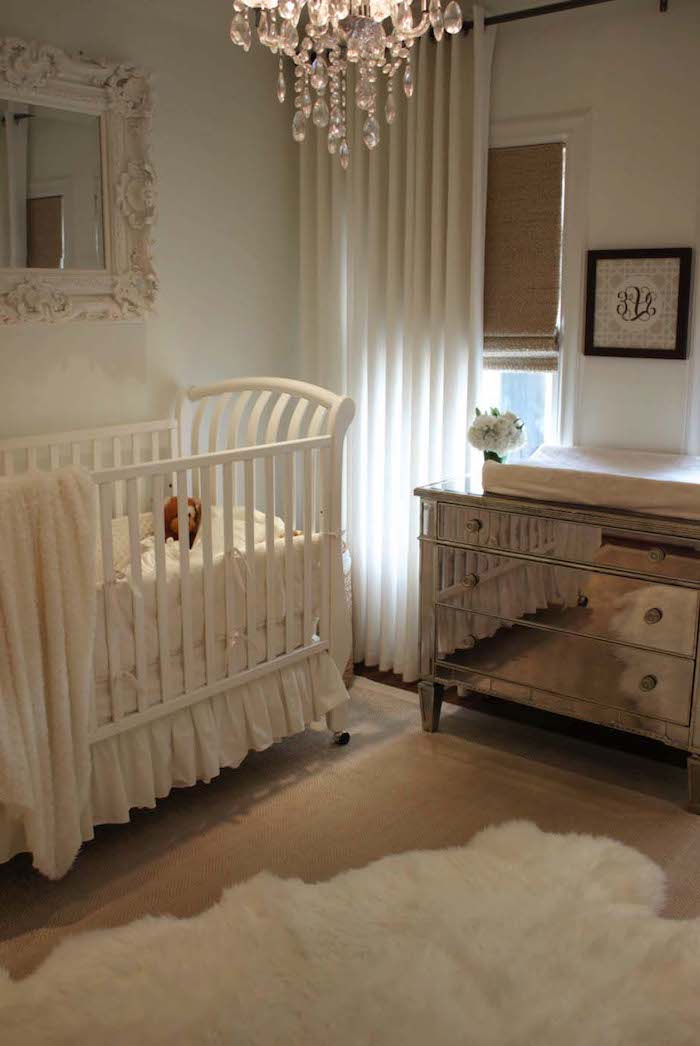 baroque framed mirror, white crystal chandelier, near mirrored chest of drawers, baby nursery with white crib, wooden floor with white lambskin rug