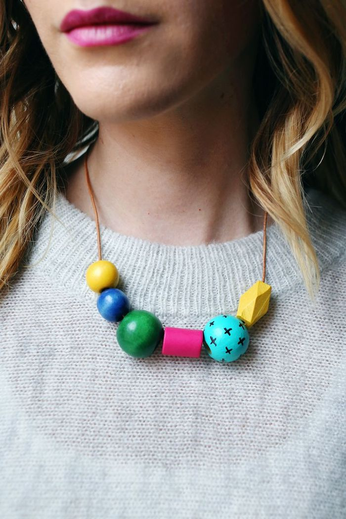 necklace made of wooden beads, in different colors and shapes, hanging around a blonde woman's neck, mother's day gift ideas, cyclamen pink lipstick