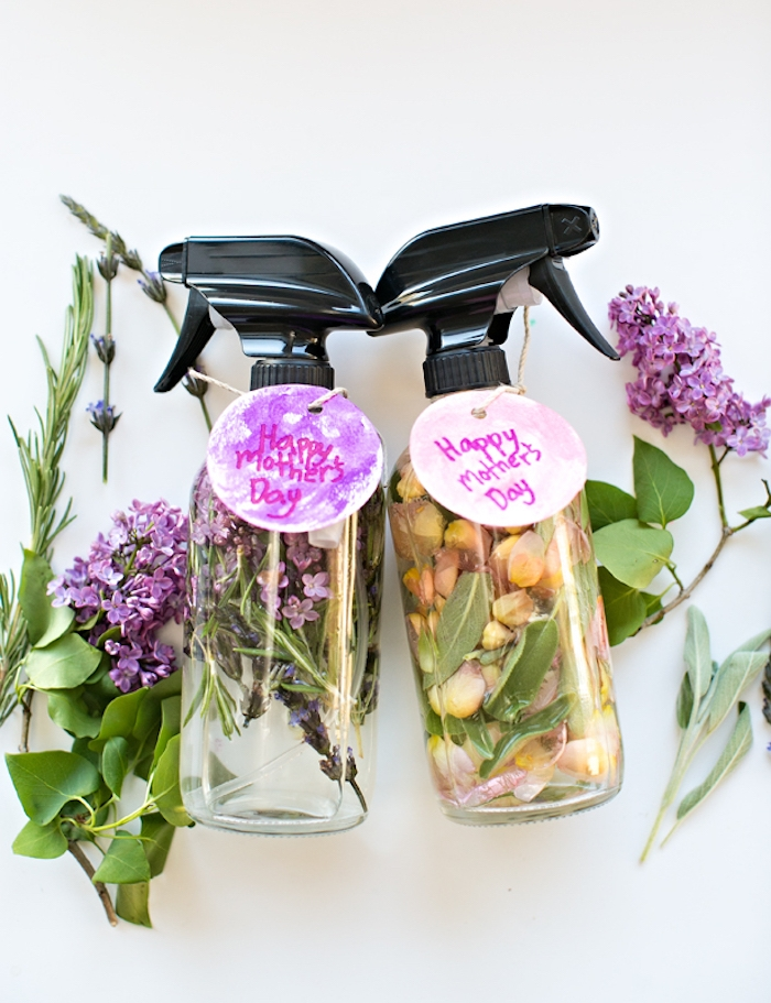 clear bottles with black, plastic spray caps, made from glass or plastic, filled with water and lilac, rose petals and herbs, mother's day gift ideas, fresh flowers nearby