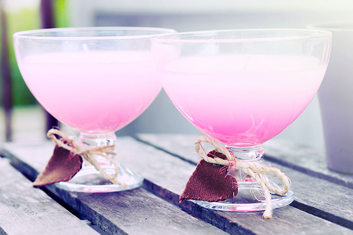 mothers day presents, two clear cocktail glasses, containing pale pink candles, decorated with dark red fabric hearts