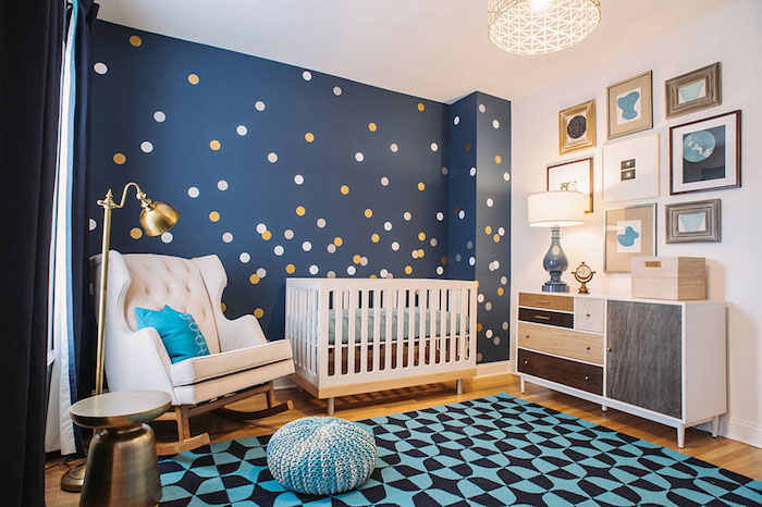 yellow and white dots, on navy blue wall, inside boy nursery, with white wooden crib, and rocking armchair
