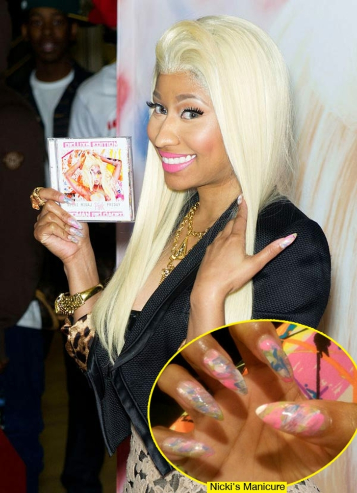 smiling nicki minaj, with smooth platinum blonde dyed hair, big fake eyelashes, bright pink lipstick, close up shows she has long, pointy nails covered with pink, blue and white paint daubs