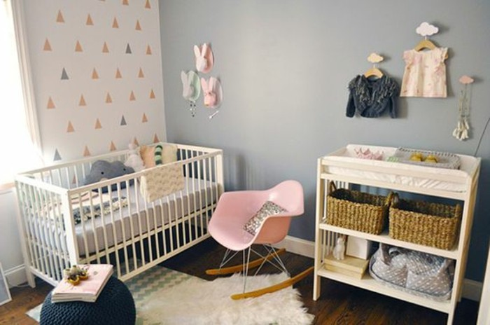 baby's nursery with blue grey paint on one wall, and light colored, patterned wallpaper on the other, pink rocking chair, various decorations in pink and gray