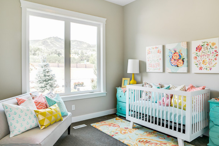 turquoise cupboards near white wooden crib, baby nursery ideas, off-white sofa, three multicolored canvases, many cushions in various colors and patterns, baby nursery ideas