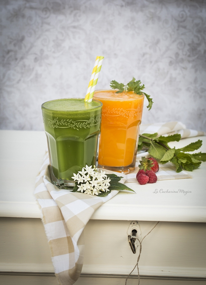 orange and green blended juice, in two clear decorated glasses, green smoothie recipe, placed on a chequered cloth, near orange blossoms, berries and mint